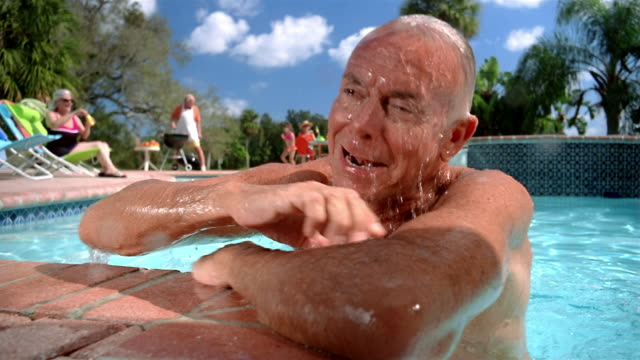 Medium shot grandfather surfacing in swimming pool / grandmother blowing bubbles and father barbecuing in background