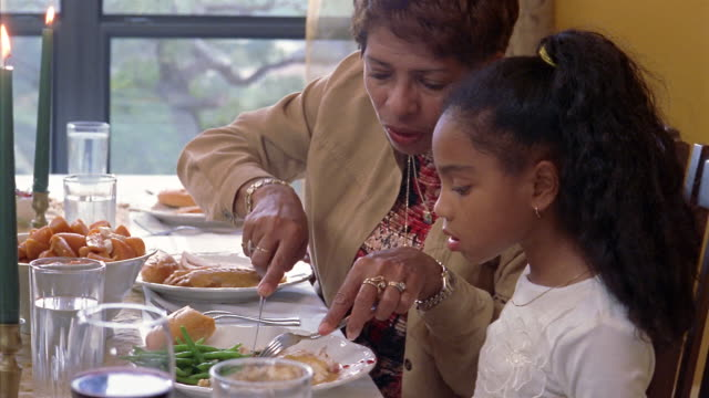 vidéos et rushes de medium shot grandmother cutting food for granddaughter at dining table during holiday meal - règle de savoir vivre