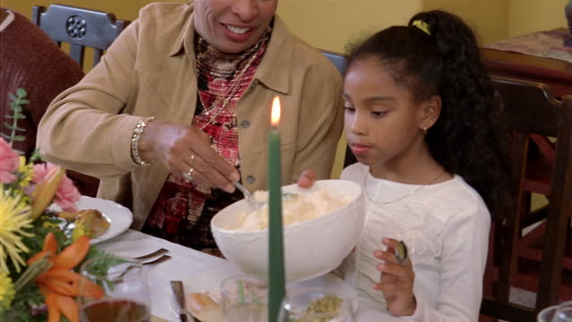 stockvideo's en b-roll-footage met medium shot grandmother serving mashed potatoes to granddaughter at dining table during holiday meal - doorgeven