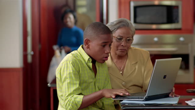 Medium shot grandmother watching grandson work on laptop in kitchen / parents entering with groceries
