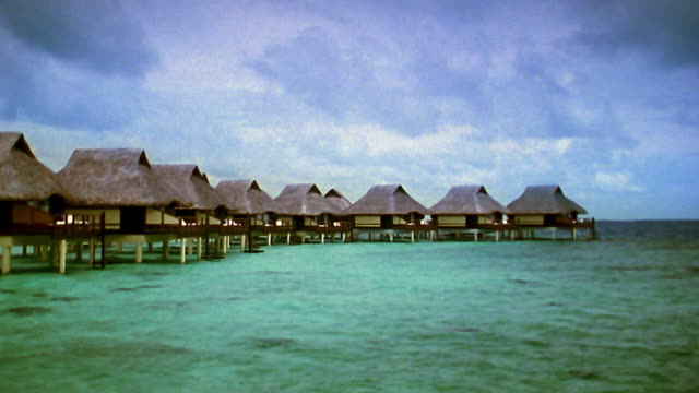 Medium shot grass huts on stilts in water resort / Tahiti