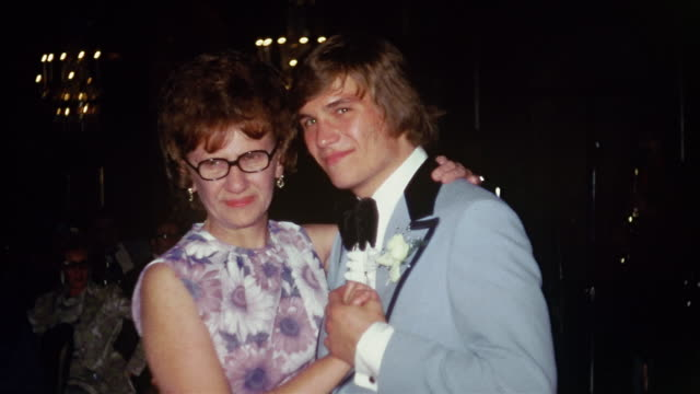 vídeos de stock e filmes b-roll de 1974 medium shot groom dancing with his mother at wedding reception / wedding guests in background - 1974