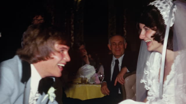 1974 medium shot groom removing garter from bride's leg at wedding reception / wedding guests in background - 1974 bildbanksvideor och videomaterial från bakom kulisserna