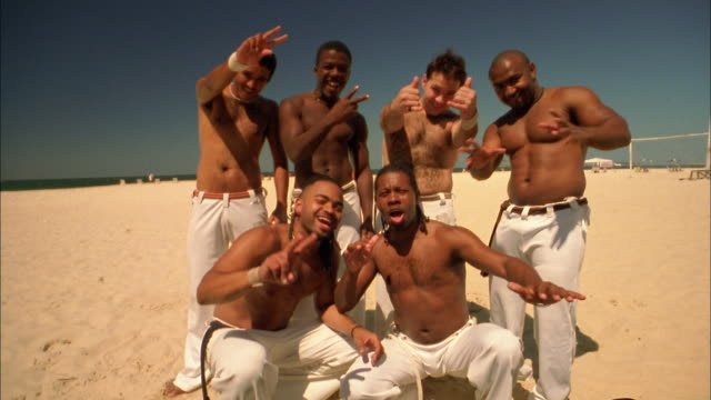 medium shot group of capoeira dancers on beach smiling and gesturing at cam / brazil - martial arts stock videos & royalty-free footage