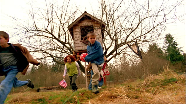 Medium shot group of children holding a ball and US flag running from tree house toward CAM