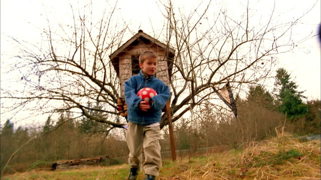 Medium shot group of children running from tree house toward CAM and holding a ball + US flag + smiling