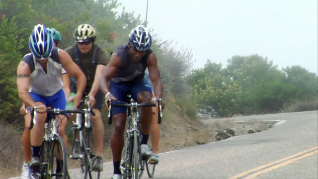 medium shot group of cyclist riding up winding road / man passing water bottle to another - five people stock videos & royalty-free footage