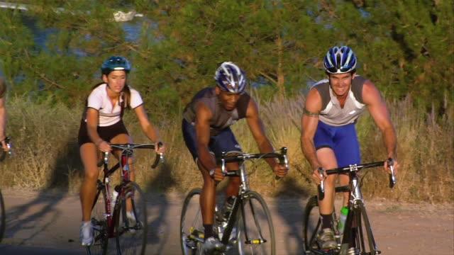 vídeos de stock, filmes e b-roll de medium shot group of cyclists biking in a line / riding uphill - colina acima