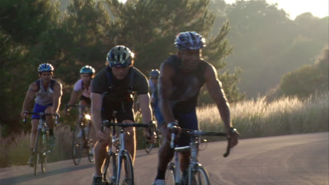 medium shot group of cyclists biking in a line / rounding a curve in the road - five people stock videos & royalty-free footage