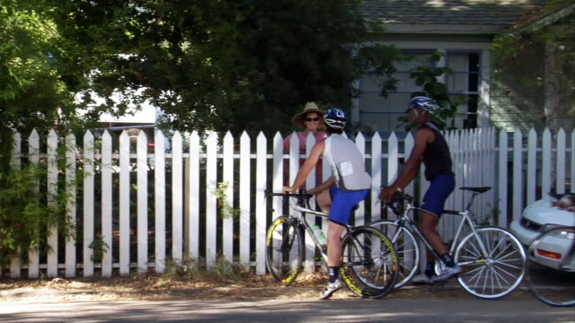 medium shot group of cyclists with map stopping to ask woman behind white picket fence for directions - eigenheim stock-videos und b-roll-filmmaterial