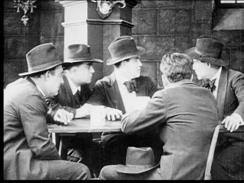1916 b/w medium shot group of men talking and scheming around table - sideways glance stock videos & royalty-free footage