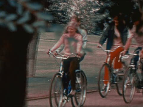 vidéos et rushes de 1970 medium shot group of multi-ethnic teenage boys and girls cycling in park / pan zoom out to wide shot / audio - 1970