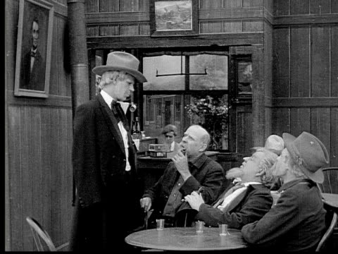 1913 b/w medium shot group of old men talking and smoking pipes around table in bar / usa  - 1913 stock videos & royalty-free footage