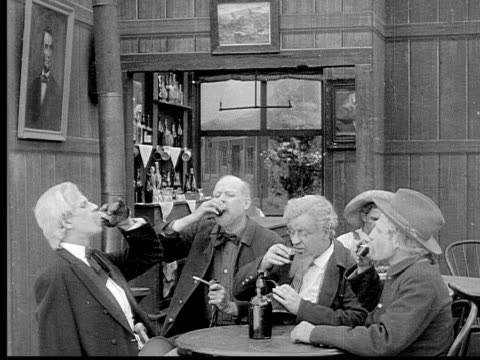 1913 B/W Medium shot Group of old men toasting, drinking and talking around table in bar / USA