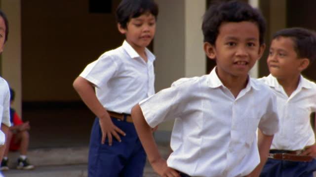 medium shot group of schoolboys exercizing outdoors - schulkind nur jungen stock-videos und b-roll-filmmaterial