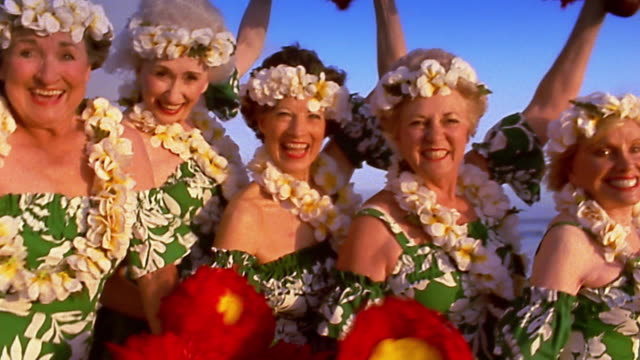 medium shot group of senior women hula dancers / ocean in background - traditional dancing stock videos and b-roll footage