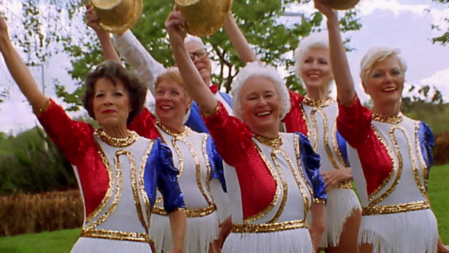 Medium shot group of seniors in red, white and blue costumes dancing outdoors
