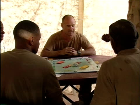 medium shot group of us soldiers playing game of monopoly / ghazni afghanistan / audio - operazione enduring freedom video stock e b–roll
