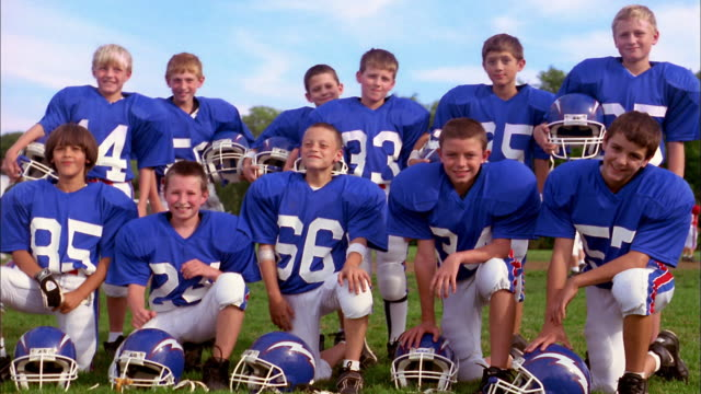 Medium shot group of young boys wearing blue football jerseys without helmets and looking at CAM