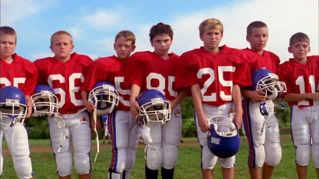 Medium shot group of young boys wearing red football jerseys, standing and looking at CAM