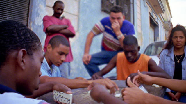 medium shot group of young hispanic men playing domino game outdoors / cuba - dominoes stock videos & royalty-free footage