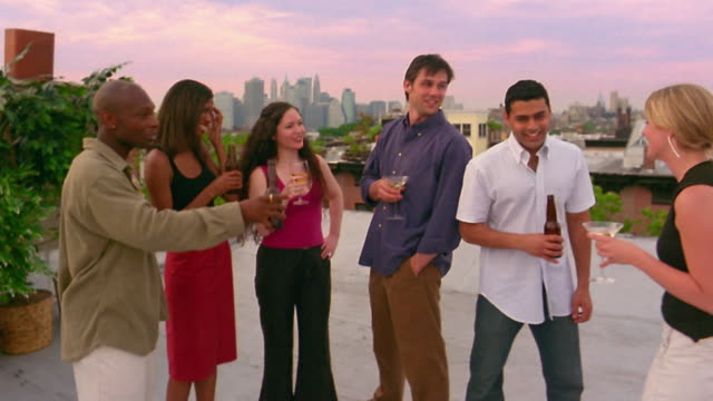 Medium shot group of young men and women having drinks on a rooftop / skyline in background / New York City