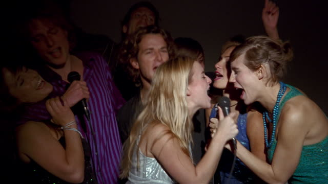 Medium shot group of young men and women singing karaoke + laughing / zoom in blonde woman with microphone