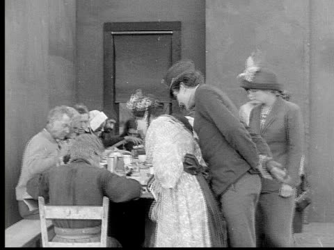 1913 b/w medium shot guard escorting women in county poor house while residents eat meal around table / usa  - 1913 stock-videos und b-roll-filmmaterial