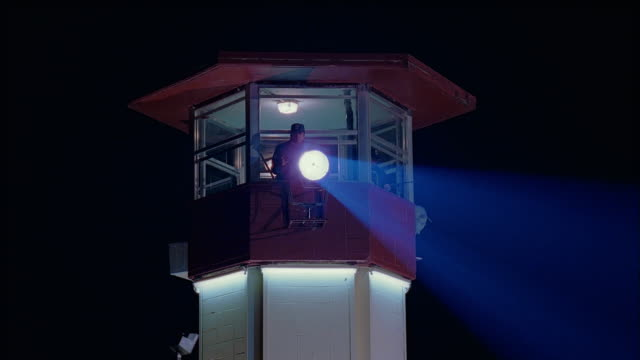 stockvideo's en b-roll-footage met medium shot guard in prison tower shining search light - 1998