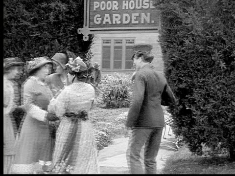 1913 b/w medium shot guide showing women garden and entering poor house / usa  - neunzehntes jahrhundert stock-videos und b-roll-filmmaterial