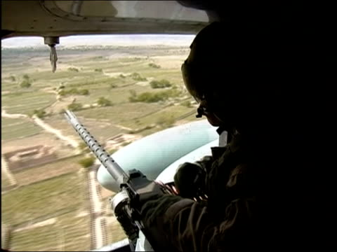 Medium shot gunner looking out of helicopter at landscape / Afghanistan / AUDIO