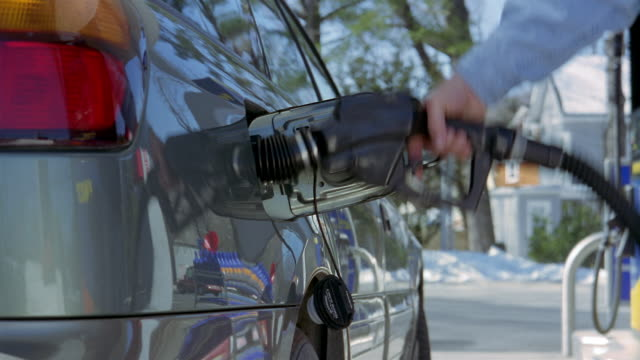 vídeos y material grabado en eventos de stock de medium shot hand placing nozzle of gas pump into gas tank of car and turning on pump / vermont - bomba de combustible