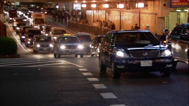 medium shot heavy traffic passing through intersection at night in shinjuku / tokyo, japan - 2005年点の映像素材/bロール