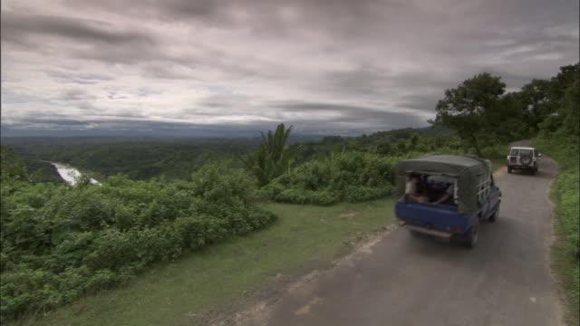 vídeos y material grabado en eventos de stock de medium shot high angle - cars driving along countryside road on cloudy day / bangladesh  - suv