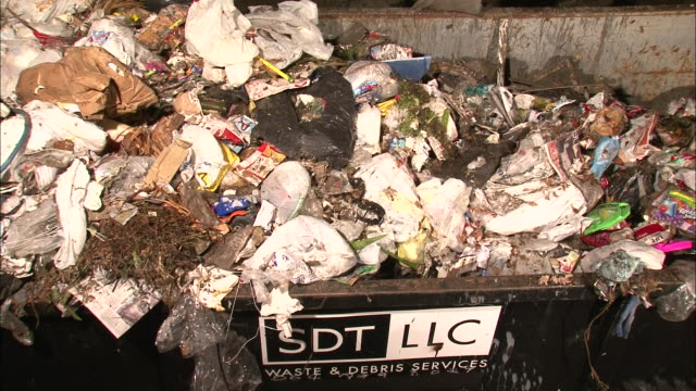 stockvideo's en b-roll-footage met medium shot high angle - trash is dumped from above into garbage receptacle / new orleans louisiana - afvalcontainer container