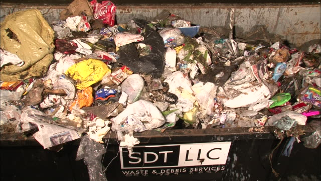 Medium Shot High Angle - Trash is dumped from above into garbage receptacle, some spills over / New Orleans Louisiana