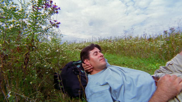 vidéos et rushes de medium shot hiker lying down for rest in field - plante sauvage