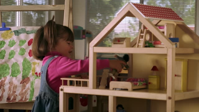 medium shot hispanic female toddler playing with dollhouse - dollhouse stock videos & royalty-free footage