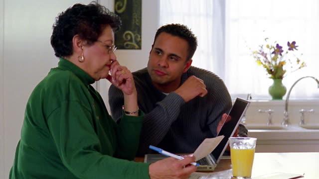 Medium shot Hispanic man helping Hispanic senior woman pay bills on laptop