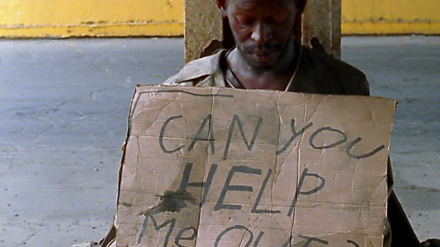 "medium shot homeless black man holding ""can you help me out?"" sign / looking up - 物を乞う点の映像素材/bロール"