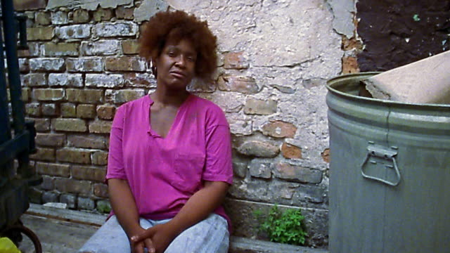 Medium shot homeless Black woman sitting against brick wall near garbage can