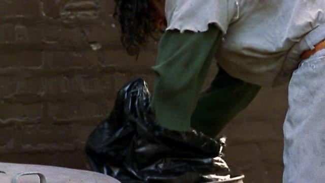 Medium shot homeless man looking through garbage can