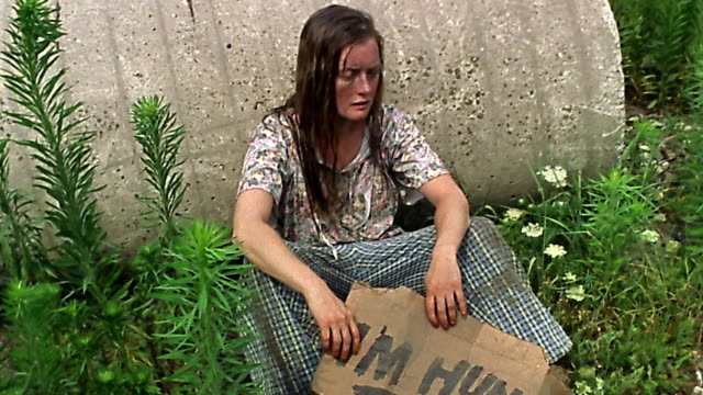 """Medium shot homeless woman sitting in weeds holding """"I'm hungry"""" sign"""