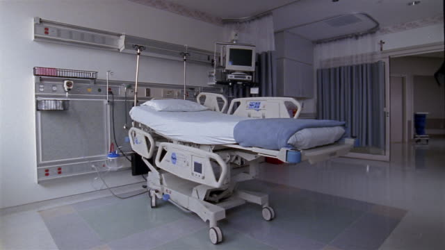 Medium shot hospital bed and equipment in room in intensive care unit