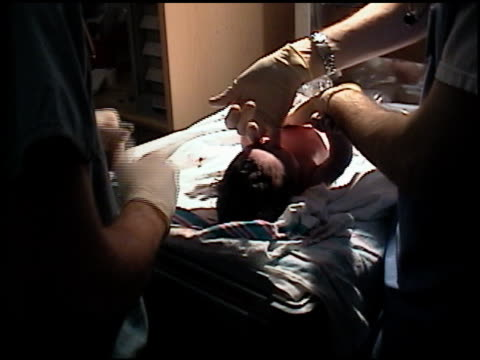 stockvideo's en b-roll-footage met medium shot hospital staff performing apgar test on newborn baby - 2003