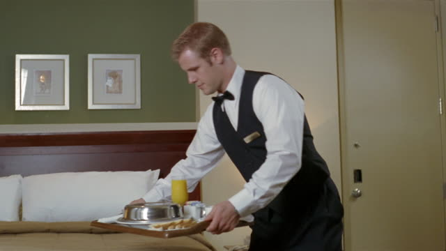 vídeos de stock e filmes b-roll de medium shot hotel employee delivering tray of room service breakfast to hotel room / placing tray on bed and removing lid - hotel