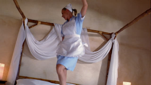 Medium shot housekeeper jumping up and down on bed in hotel room