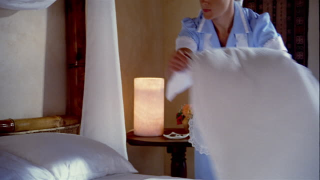 medium shot housekeeper making bed in hotel room / placing tray of chocolates on bed - pillow stock videos & royalty-free footage