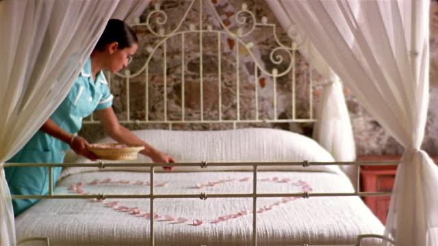 stockvideo's en b-roll-footage met medium shot housekeeper making heart on bedspread with flower petals - dubbel bed