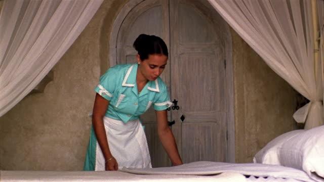 vídeos y material grabado en eventos de stock de medium shot housekeeper turning down bed - hospitalidad